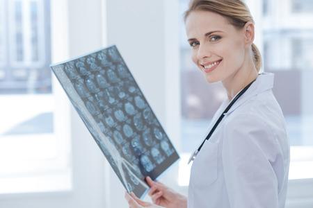 Charmante röntgenspecialist die röntgenresultaten onderzoekt bij het laboratorium Stockfoto