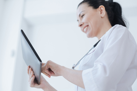 Cheerful therapist using tablet for work in the clinic