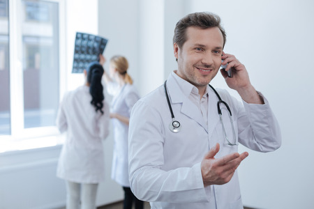 Concentrated doctor using modern smartphone in the clinic Stock Photo