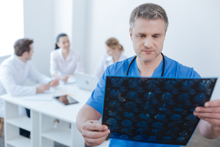Serious neurologist examining mrt scan photo at the laboratory