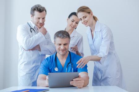 Delighted medics enjoying new digital gadget at work