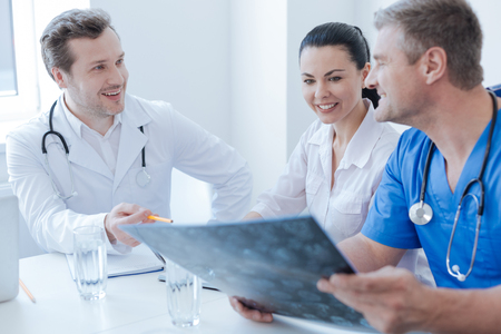 Experienced neurologists discussing x ray photo at the clinic