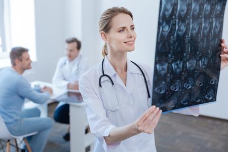Hermoso neurólogo examinando la foto de rayos x en la clínica