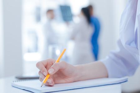 diligente: Diligente médico tomando notas en la clínica