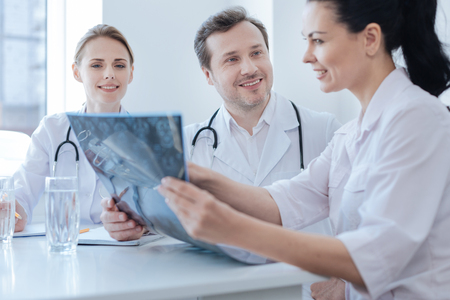 Experienced neurosurgeon helping new colleagues at the clinic