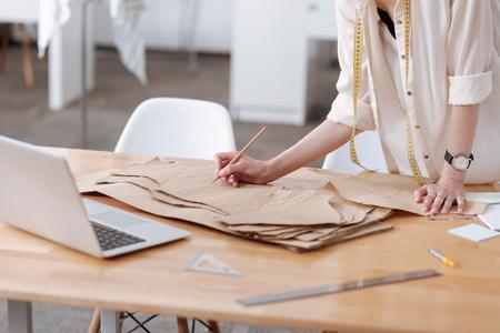 Vrouwelijke handen die op een kleding-patroon schrijven Stockfoto