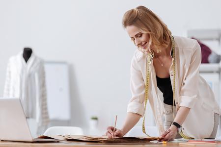 Mooie vrouw die op een kleding-patroon schrijft Stockfoto