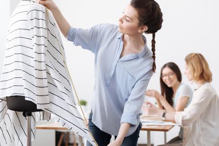 Elegant professional tailor measuring a cardigan
