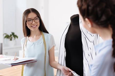 Glimlachende donkerbruine kleermaker die een staart van cardigan houdt Stockfoto