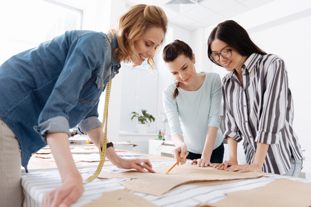 Three female tailors looking at patterns Stock Photo