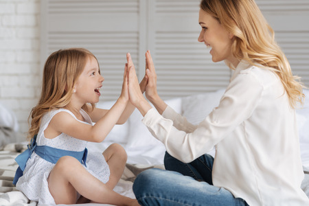 Pretty little daughter giving a high ten to her mother