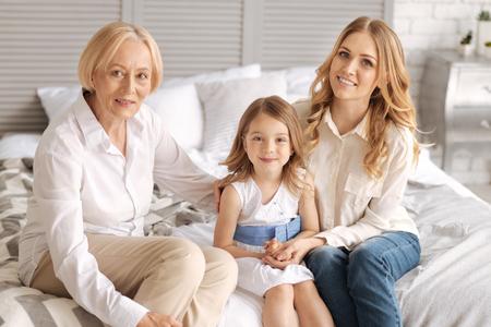 Charming three generations of women bonding Stock Photo