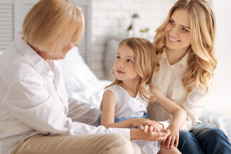 upbringing: Cute little girl socializing with her pleasant grandmother Stock Photo