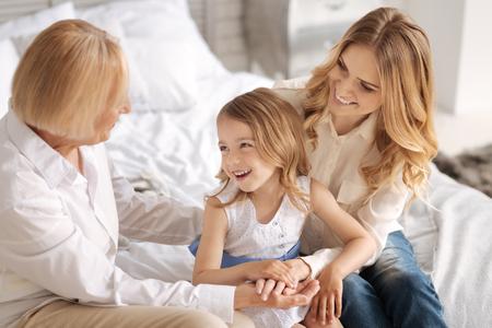 Lovely grandchild listening to her grandmother telling jokes