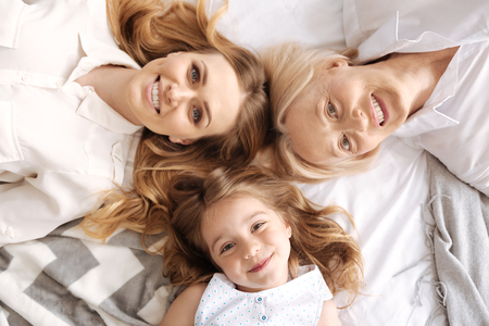 Charming three females of different age lying head to head Stock Photo