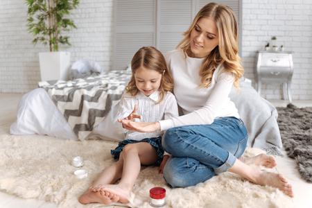 Little daughter applying cream on the mothers hand Foto de archivo