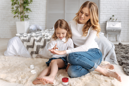 Little daughter applying cream on the mothers hand Banque d'images