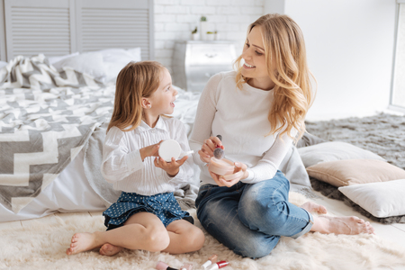 Young mother and her daughter discussing cosmetics