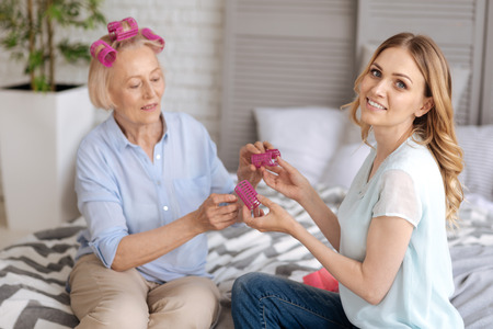 upbringing: Senior woman taking away pink hair rollers