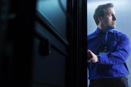 Nice serious man opening the door Stock Photo