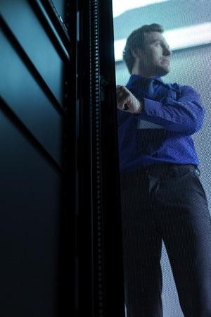 Handsome good looking man standing behind the door
