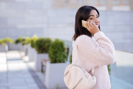 Active emotional lady talking to someone on the phone