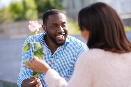 Creative courteous man giving his lady a pretty flower