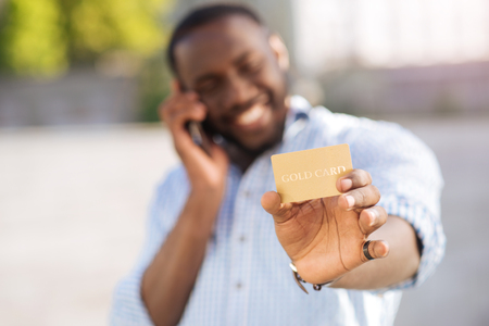 Optimistic inspired guy holding a credit card