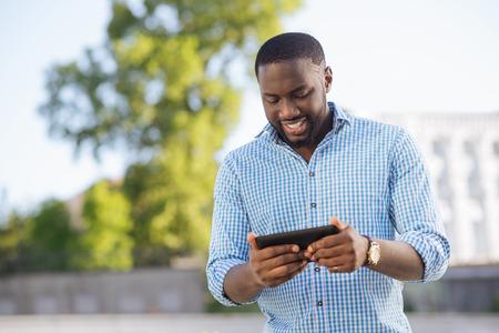 Lively dynamic man using his smartphone for entrainment