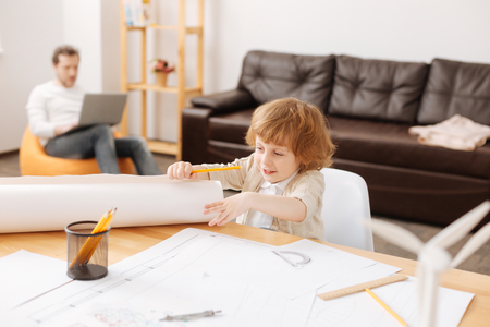 Positive delighted boy unrolling big sheet of paper