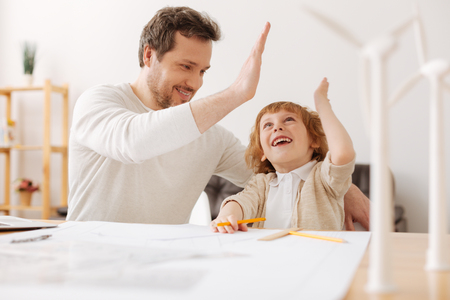 Attractive man-child looking upwards while talking to his dad Stock Photo