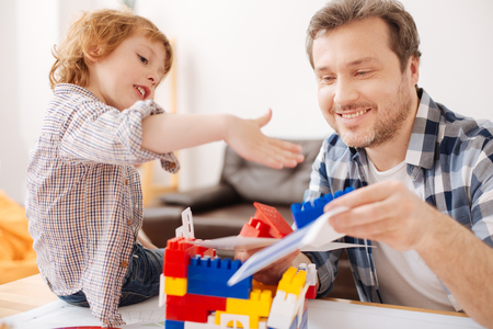 Positive delighted bearded man playing with his child Stock Photo