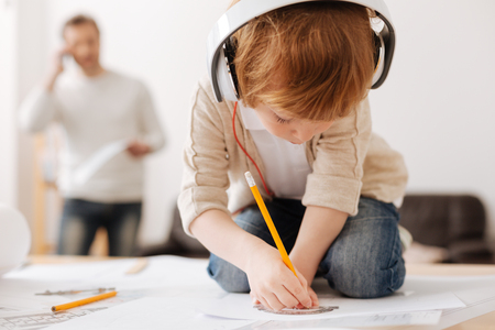 bowing head: Attentive boy bowing head while drawing picture Stock Photo