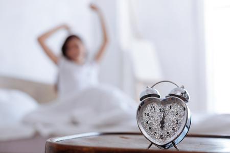 Primo piano di sveglia orologio e donna che si estende dietro Archivio Fotografico - 80505221