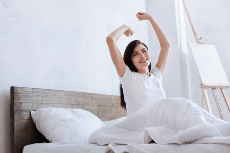Happy young lady stretching arms in bed