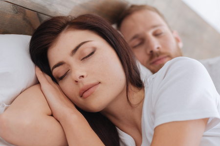 Portrait of young romantic couple sleeping in bed
