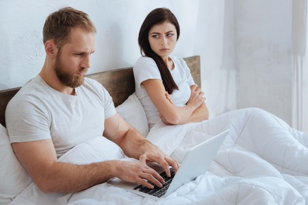 Man with laptop ignoring his frustrated girlfriend