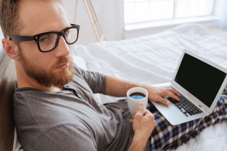 Bearded man sitting on bed with coffee and laptop