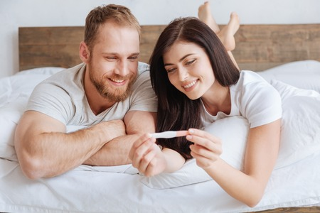 Radiant couple looking at pregnancy test in bed Stok Fotoğraf