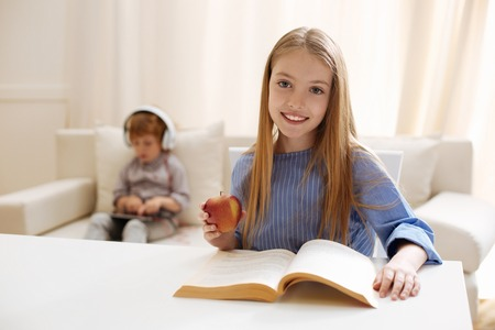 Persistent active girl working on her home assignment Stock Photo