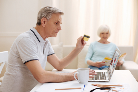 Thoughtful lively man choosing some products online