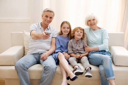 Positive vibrant family watching a movie together Stock Photo