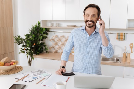 role model: Pleasant man talking on the phone in the kitchen Stock Photo