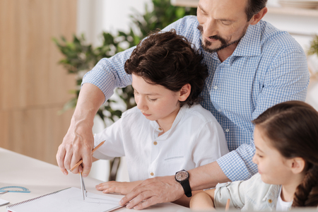 Happy loving father helping his son with math