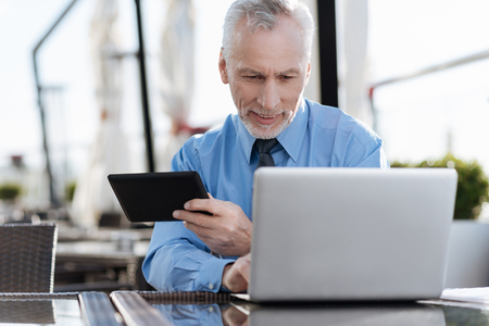 Positive delighted elderly worker sitting at his workplace Stock Photo