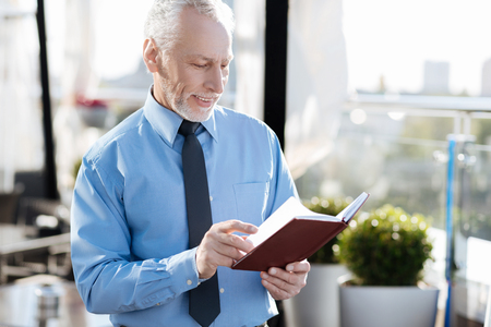 manhood: Positive delighted bearded man paging his notebook