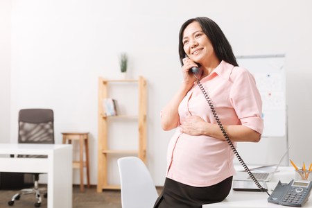 Happy pregnant woman talking on phone in the office
