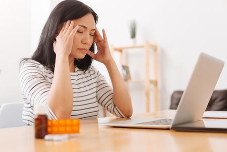 Sick woman havign a terrible head ache