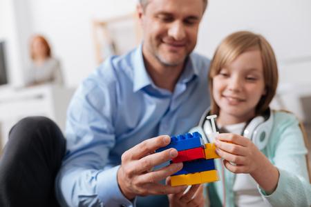 Gelukkige houdende van papa die zijn kind helpt dat iets bouwt