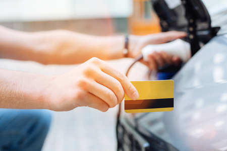 Male hand holding a credit card while charging an electric car Stock Photo